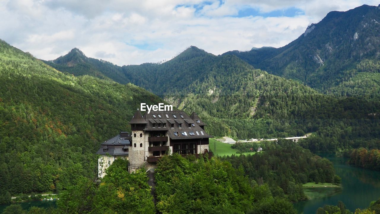 mountain, plant, architecture, building exterior, tree, built structure, mountain range, beauty in nature, scenics - nature, sky, building, nature, green color, cloud - sky, no people, day, tranquil scene, growth, house, tranquility, outdoors