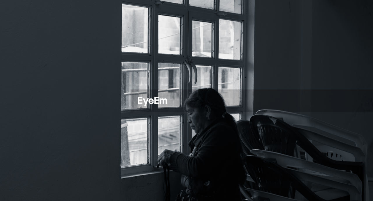 window, real people, one person, indoors, lifestyles, transparent, day, adult, leisure activity, glass - material, sitting, three quarter length, women, dark, standing, domestic room, casual clothing, contemplation