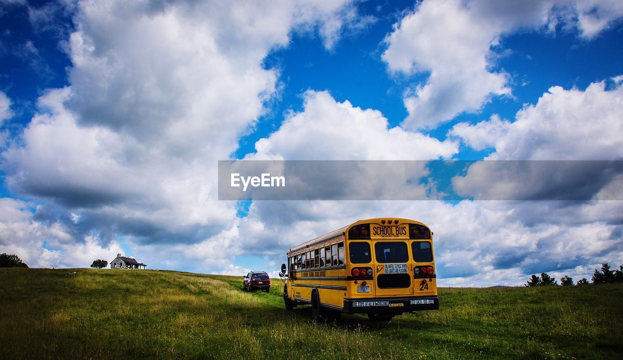 transportation, land vehicle, sky, cloud - sky, mode of transport, school bus, bus, day, field, nature, grass, public transportation, yellow, outdoors, landscape, no people, beauty in nature