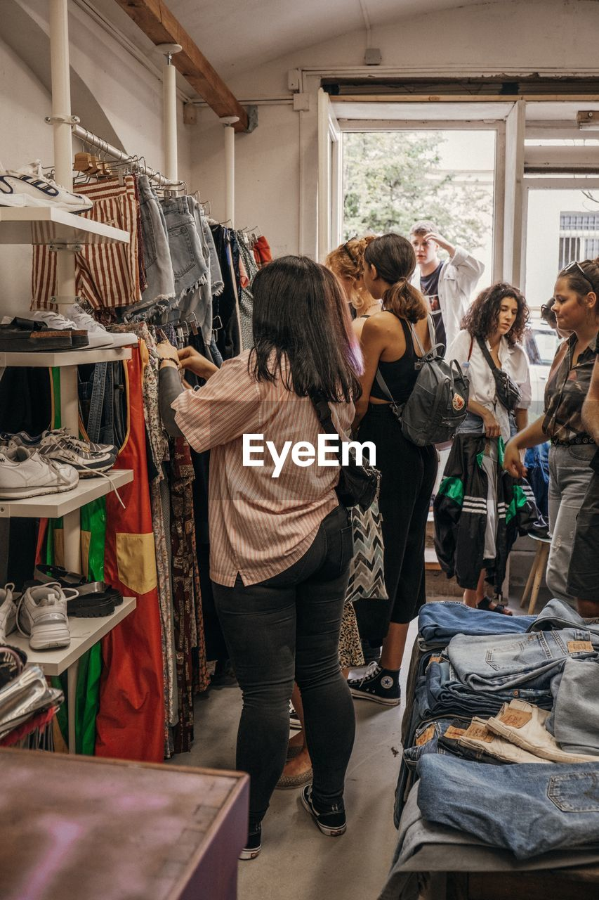 women, adult, retail, shopping, choice, standing, indoors, lifestyles, men, business, group of people, small business, rack, people, clothing, store, real people, fashion, clothing store, young adult, decisions, sale, consumerism