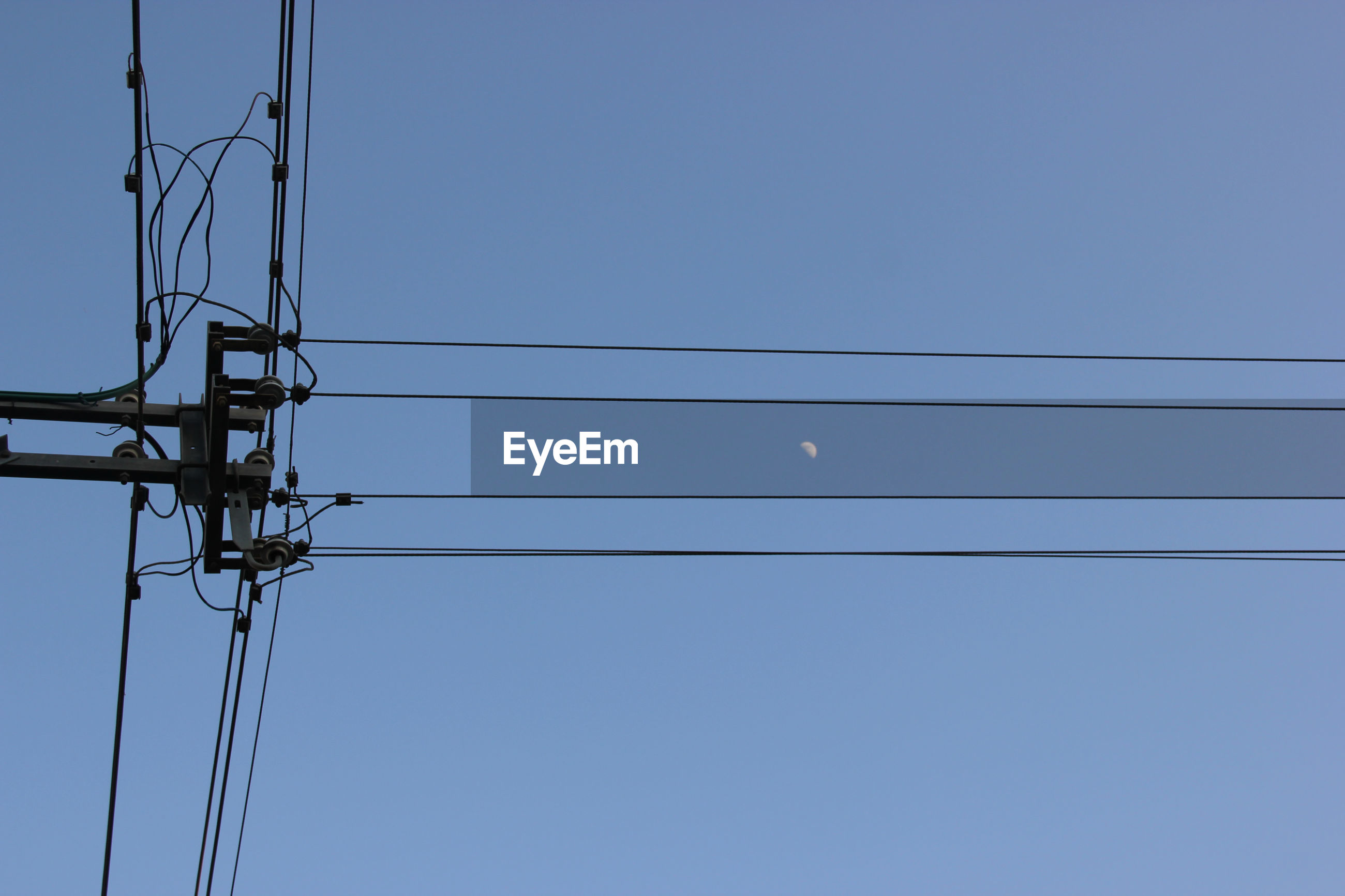 Low angle view of electricity pylon against clear blue sky