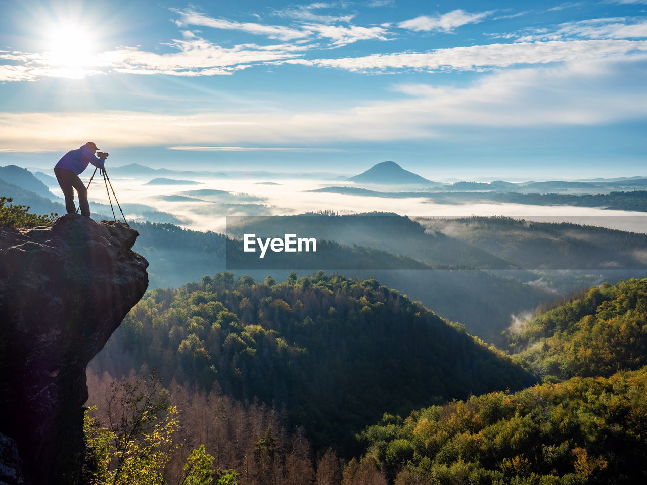 Photographer on mountain witch through viewfinder. morning landscape from top of the mountain
