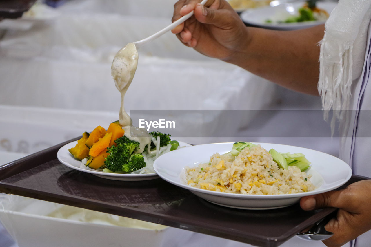 food, food and drink, real people, plate, human hand, freshness, hand, one person, holding, vegetable, ready-to-eat, midsection, kitchen utensil, table, healthy eating, indoors, occupation, serving size, wellbeing, chef, temptation
