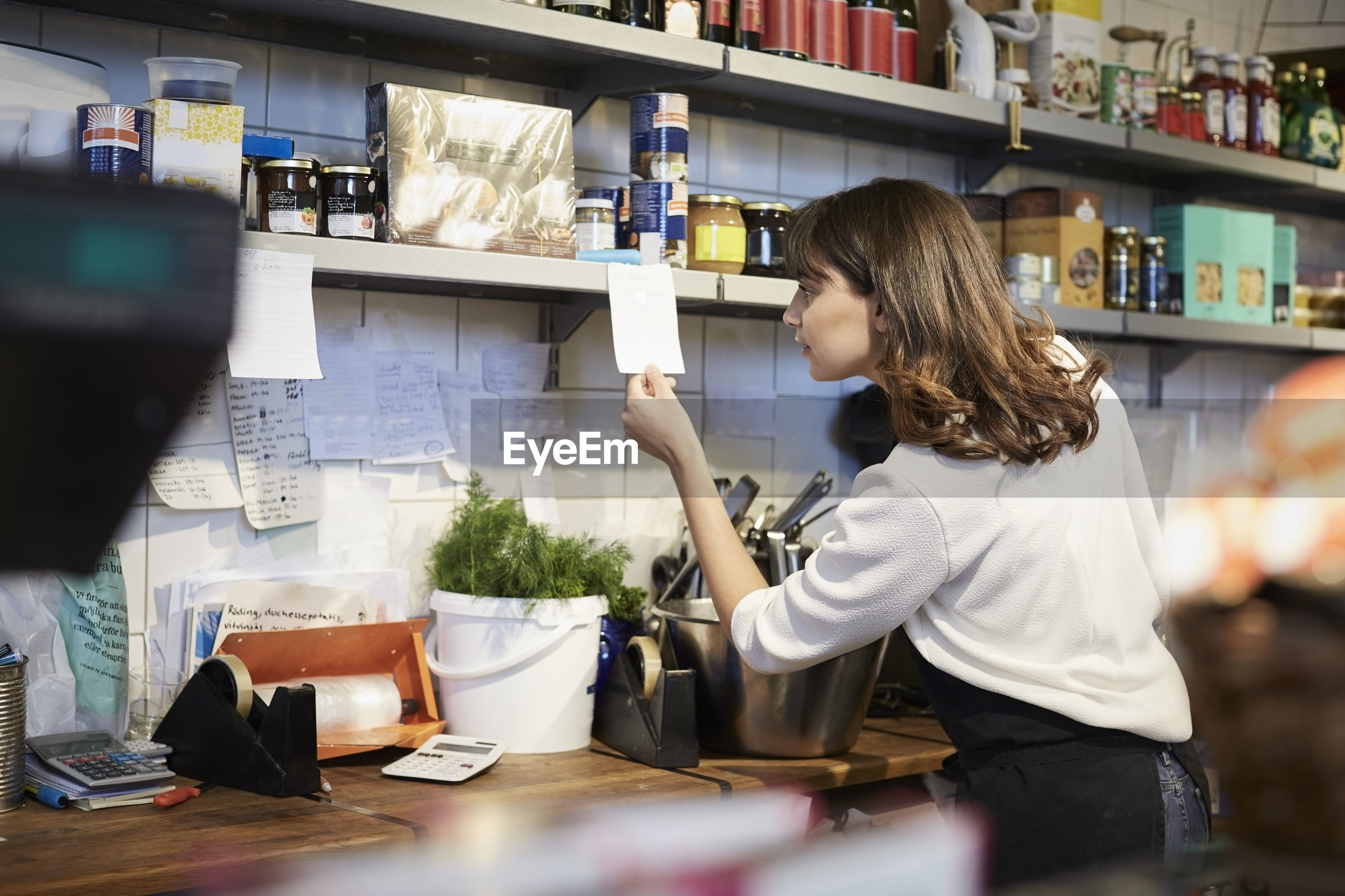 MIDSECTION OF WOMAN STANDING AT RESTAURANT