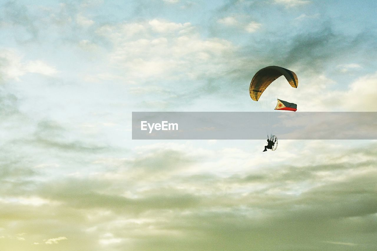 LOW ANGLE VIEW OF PARACHUTE FLYING AGAINST CLOUDY SKY