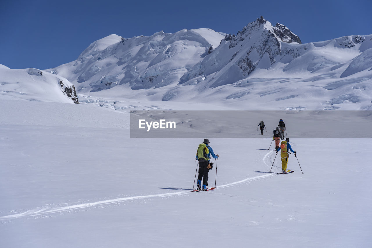 PEOPLE SKIING ON SNOWCAPPED MOUNTAIN AGAINST MOUNTAINS