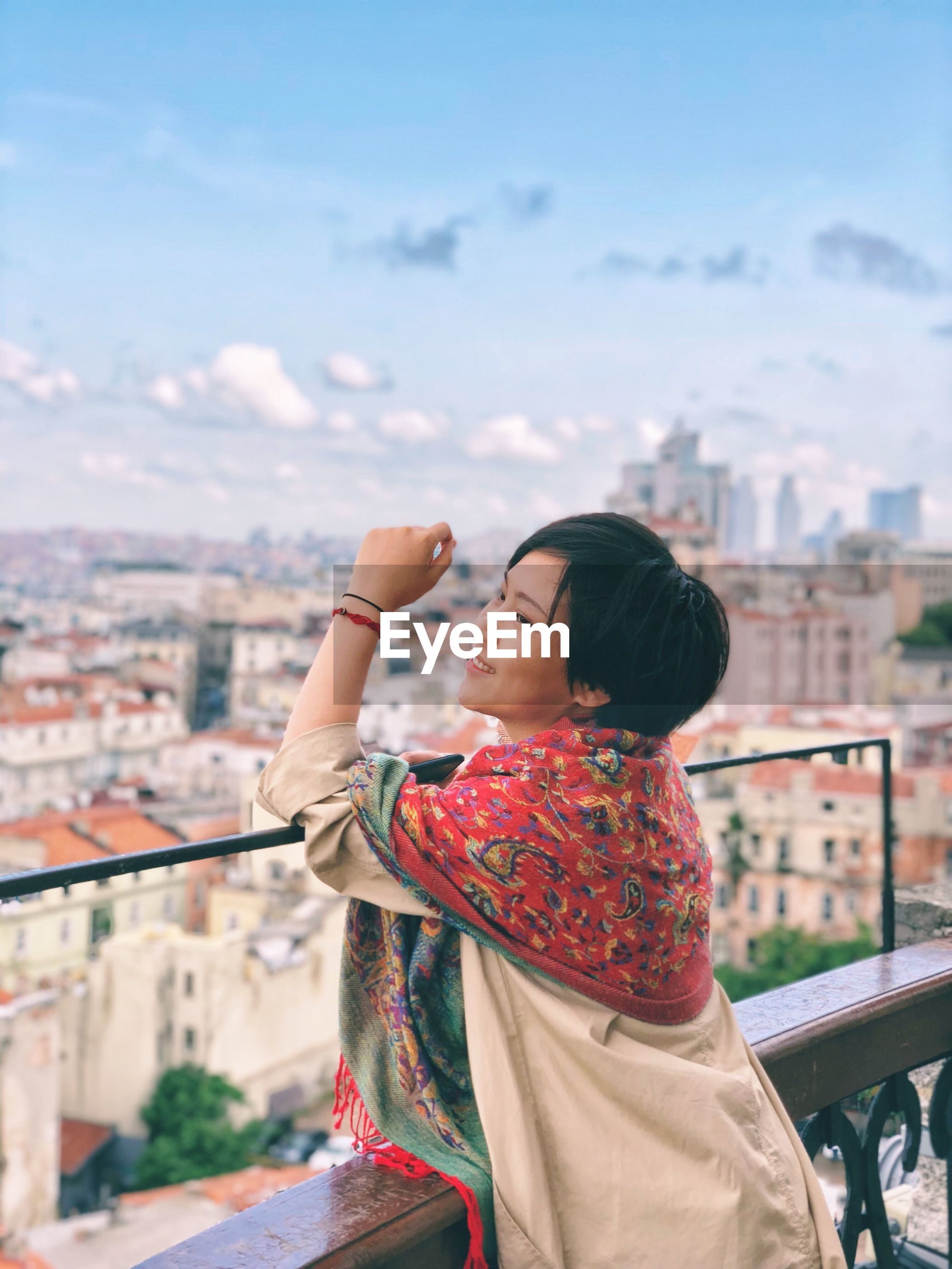 Smiling young woman looking at city against sky