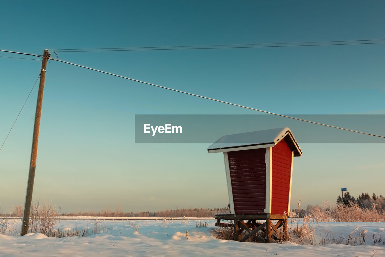 Built Structure By Telephone Pole On Snowy Field Against Clear Sky