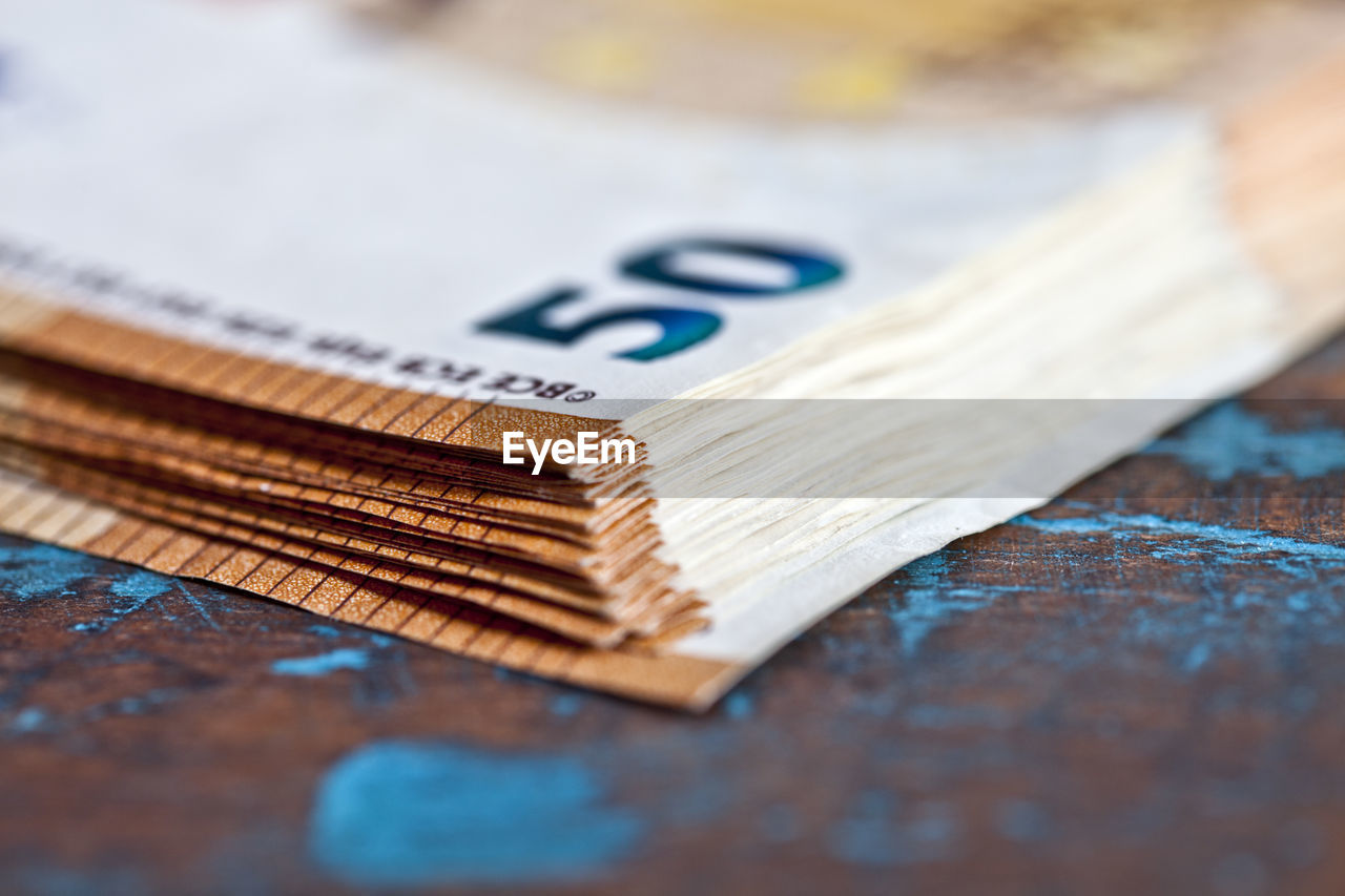 selective focus, still life, table, close-up, wood - material, no people, indoors, blue, number, high angle view, communication, brush, text, currency, western script, paintbrush, art and craft, capital letter, finance, cutting board
