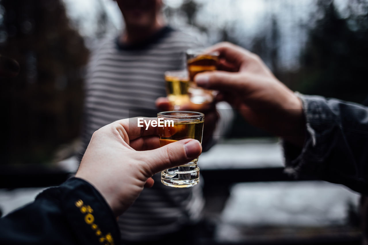 human hand, holding, hand, drink, real people, refreshment, human body part, alcohol, food and drink, adult, leisure activity, glass, lifestyles, men, women, people, beer, two people, drinking glass, celebration, cocktail, finger