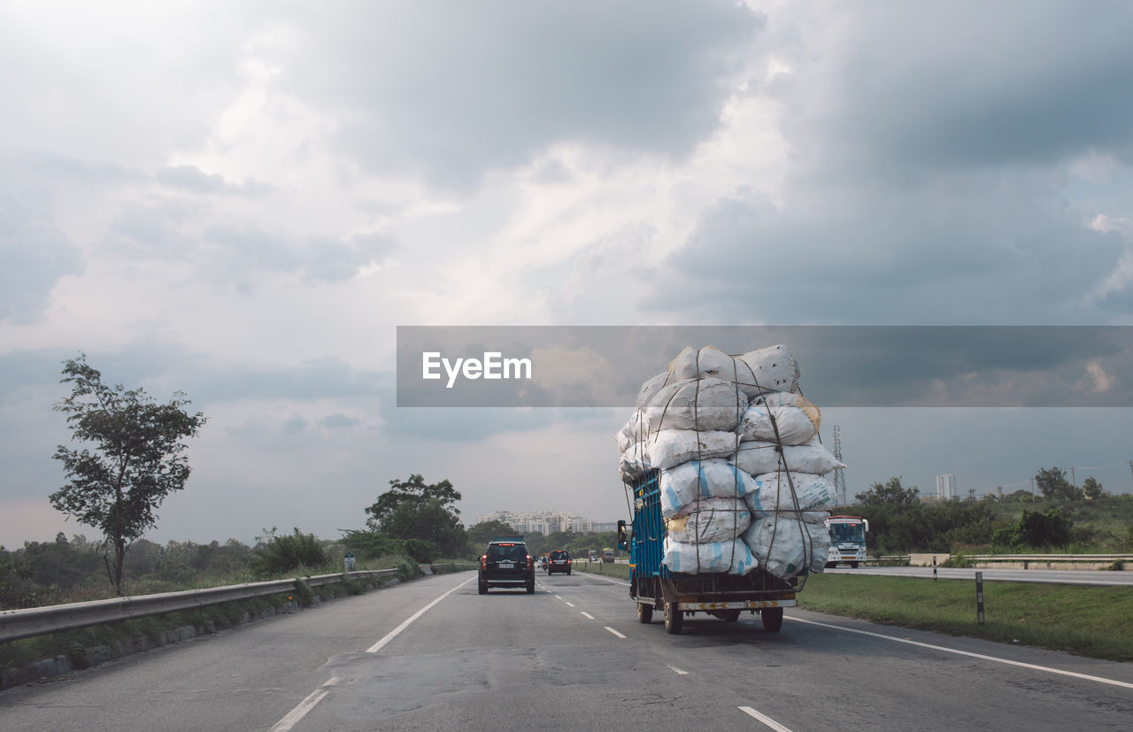 transportation, cloud - sky, road, sky, land vehicle, mode of transportation, day, motor vehicle, direction, the way forward, truck, nature, semi-truck, tree, outdoors, no people, sign, on the move, car, diminishing perspective
