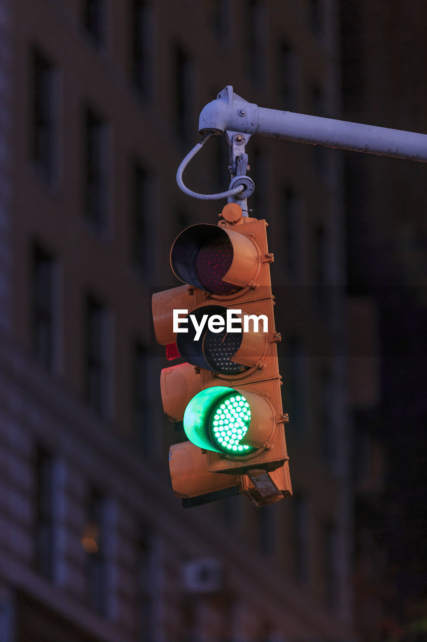 focus on foreground, architecture, no people, sign, communication, built structure, stoplight, building exterior, outdoors, close-up, safety, green light, illuminated, metal, light, day, road signal, hanging, city, guidance