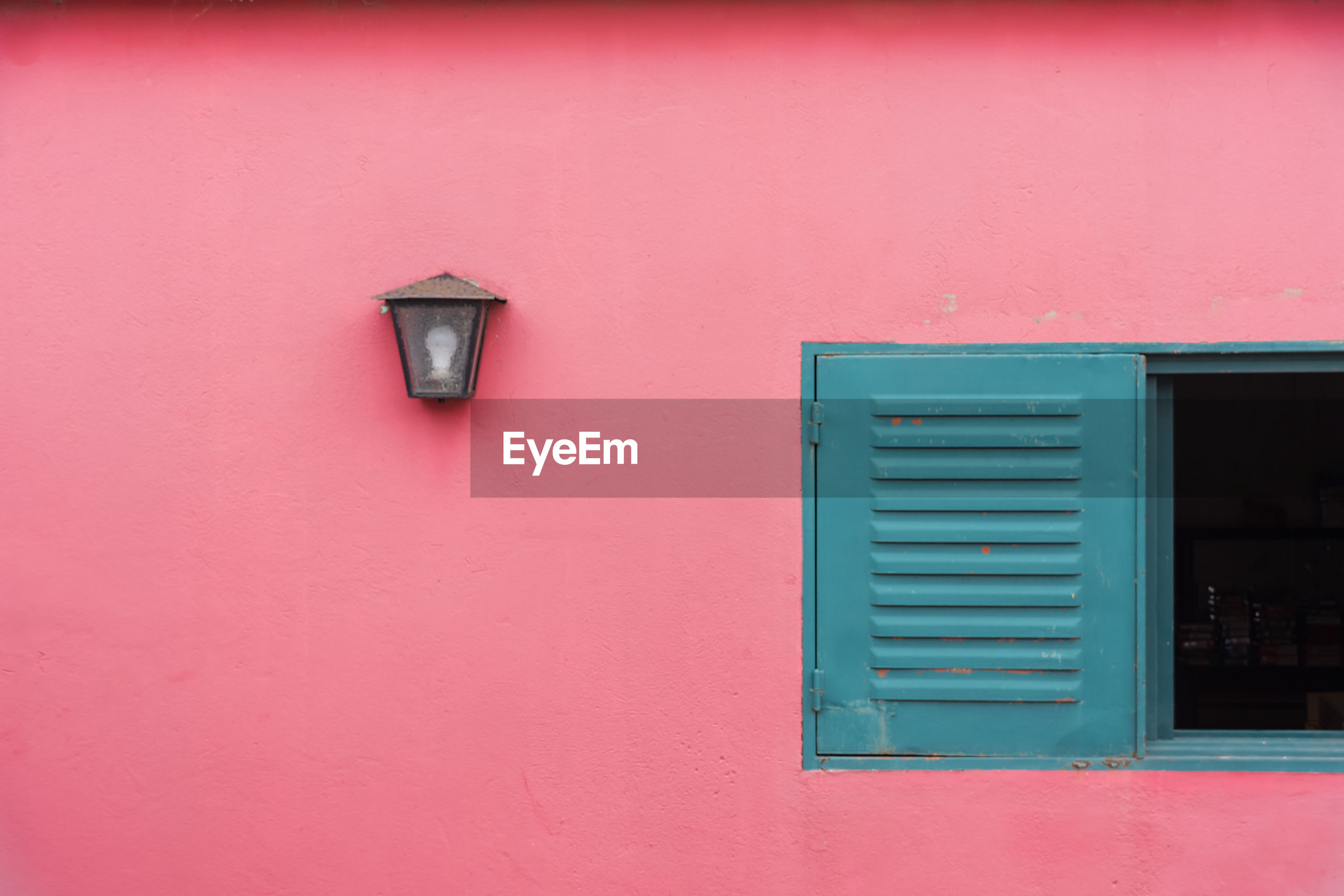 Scenic view of a closed windows next to a lamp on a pink wall