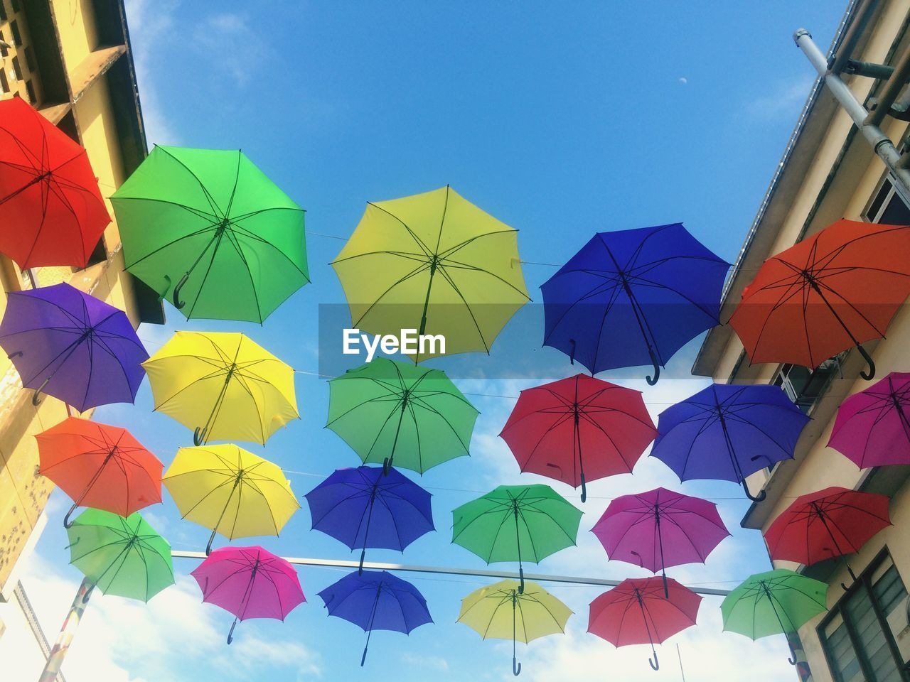protection, umbrella, multi colored, sky, low angle view, security, day, no people, nature, choice, variation, hanging, side by side, outdoors, large group of objects, clear sky, pattern, architecture, creativity