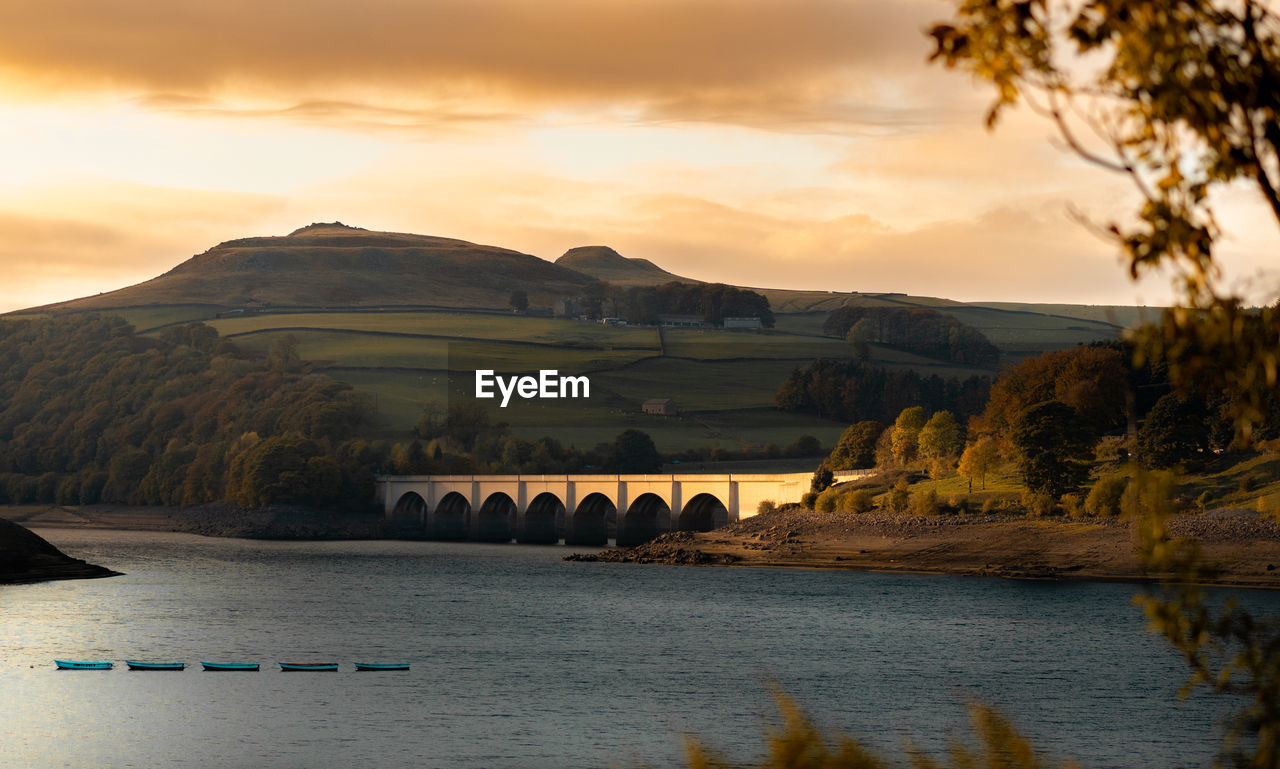 sky, water, sunset, mountain, cloud - sky, beauty in nature, scenics - nature, river, nature, architecture, waterfront, built structure, transportation, no people, tranquil scene, bridge, connection, tranquility, tree, bridge - man made structure, arch, outdoors, arch bridge
