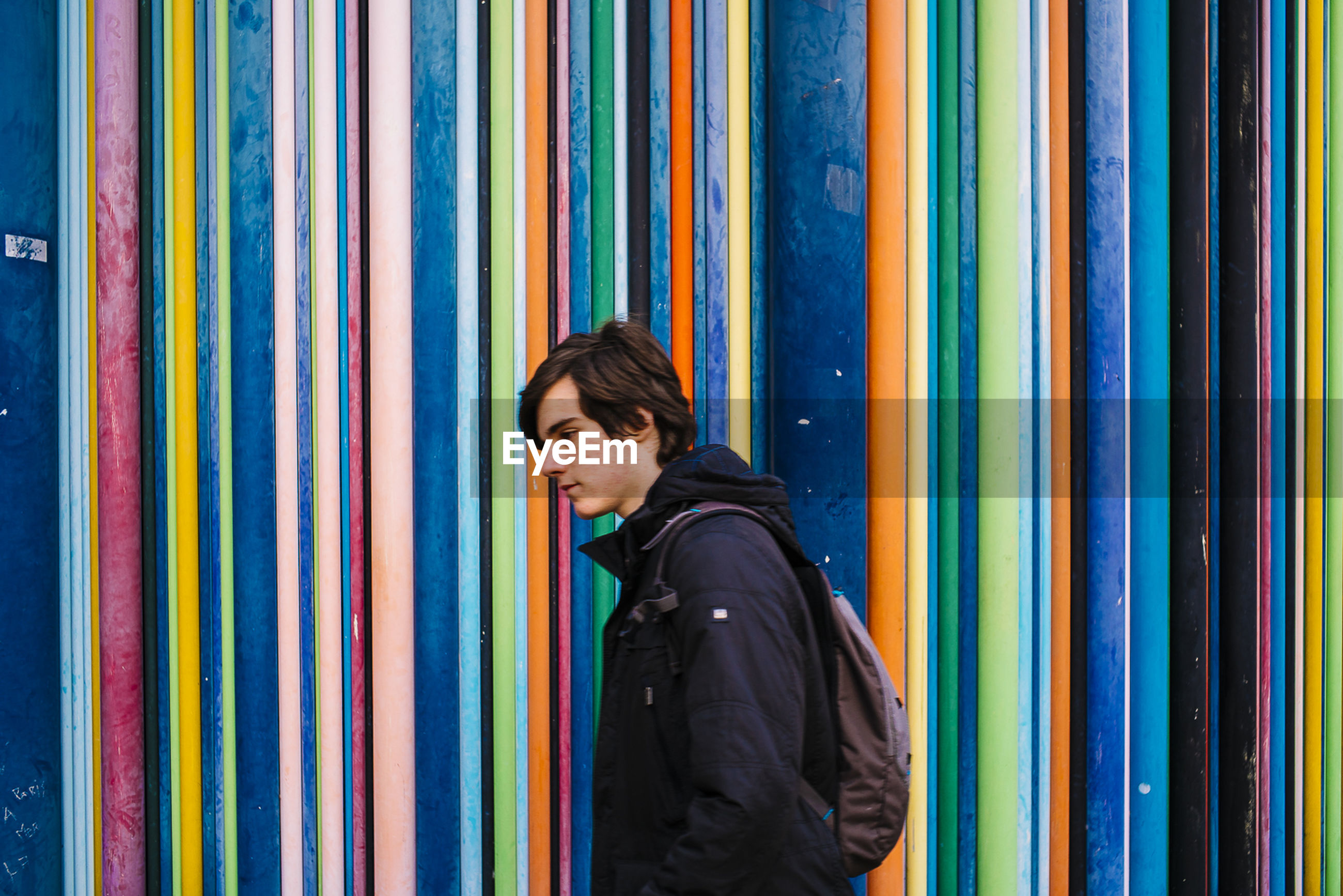 Handsome man walking against colorful wall