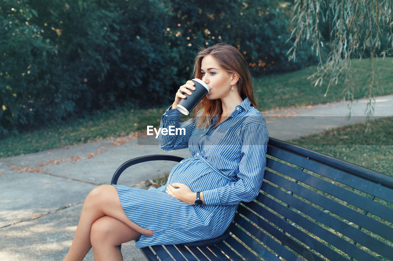 Pregnant woman drinking coffee while sitting on bench at park