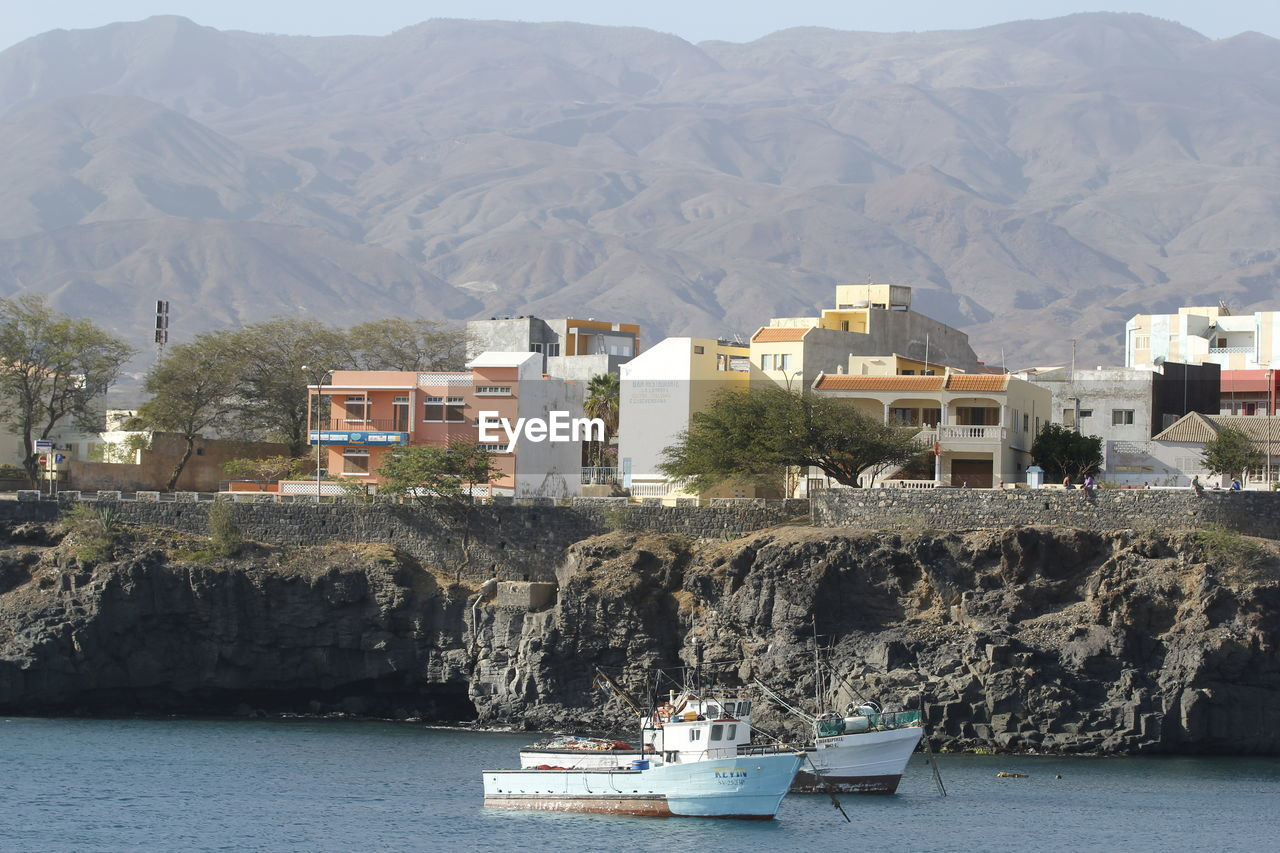 Scenic View Of Sea By Buildings And Mountains