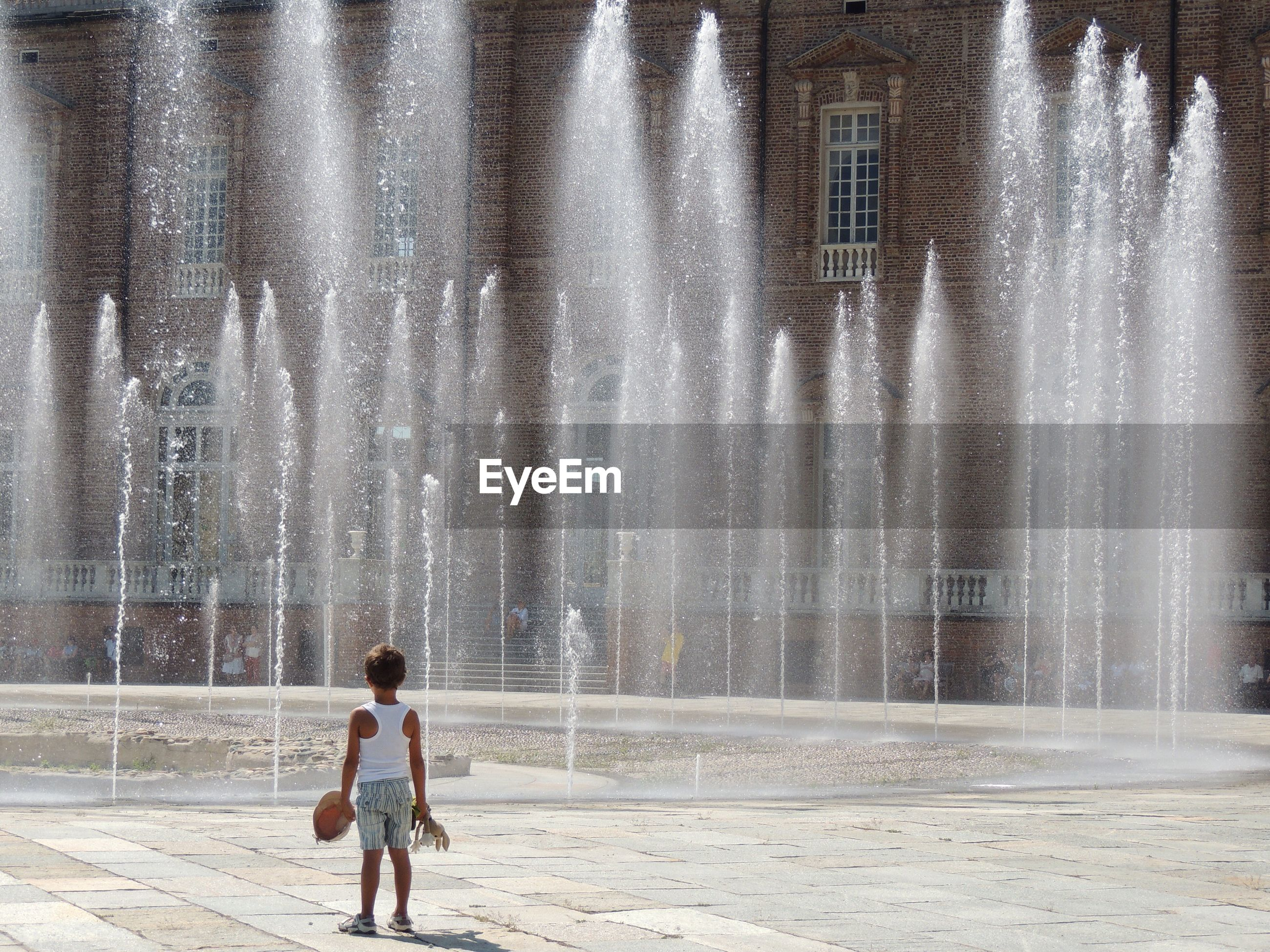 Rear view of boy standing against fountain
