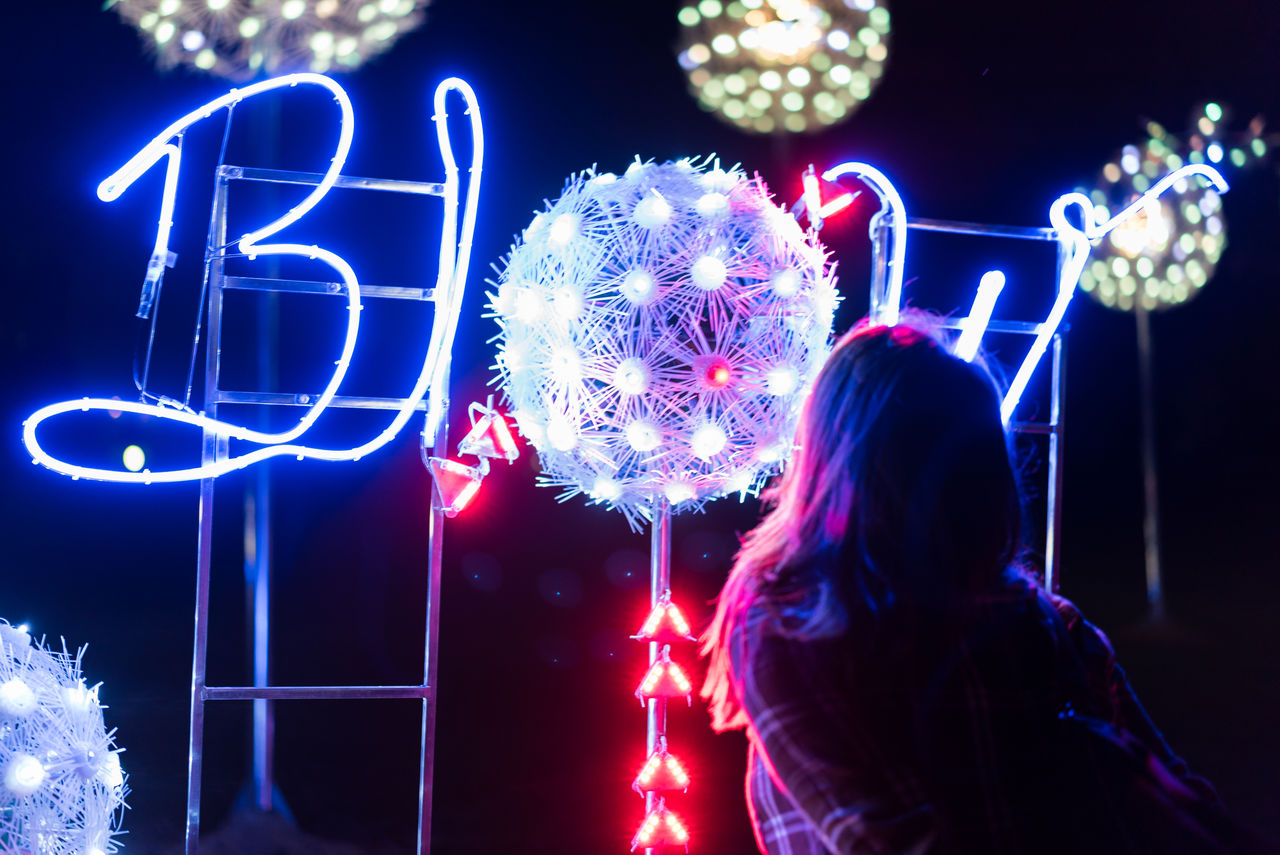 night, illuminated, real people, rear view, arts culture and entertainment, one person, lifestyles, leisure activity, event, outdoors, multi colored, standing, women, excitement, city, people