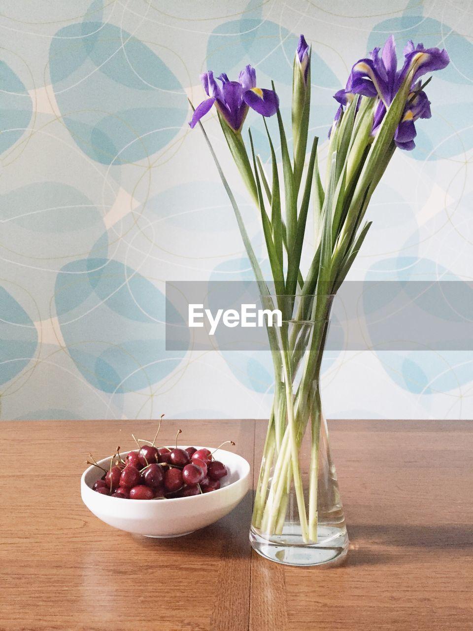 Iris Flowers In Vase By Cherries On Table