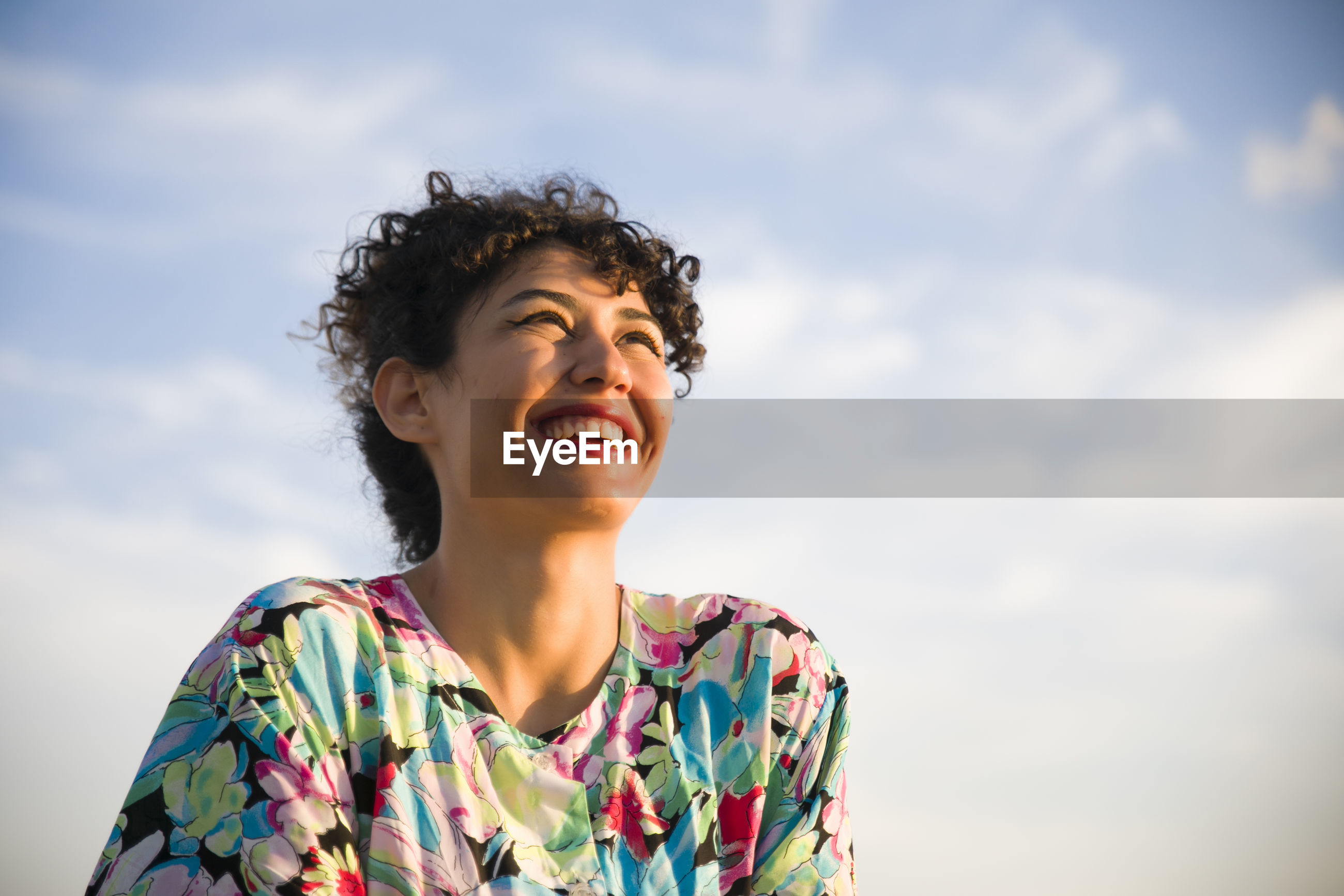 Low angle view of cheerful woman against cloudy sky