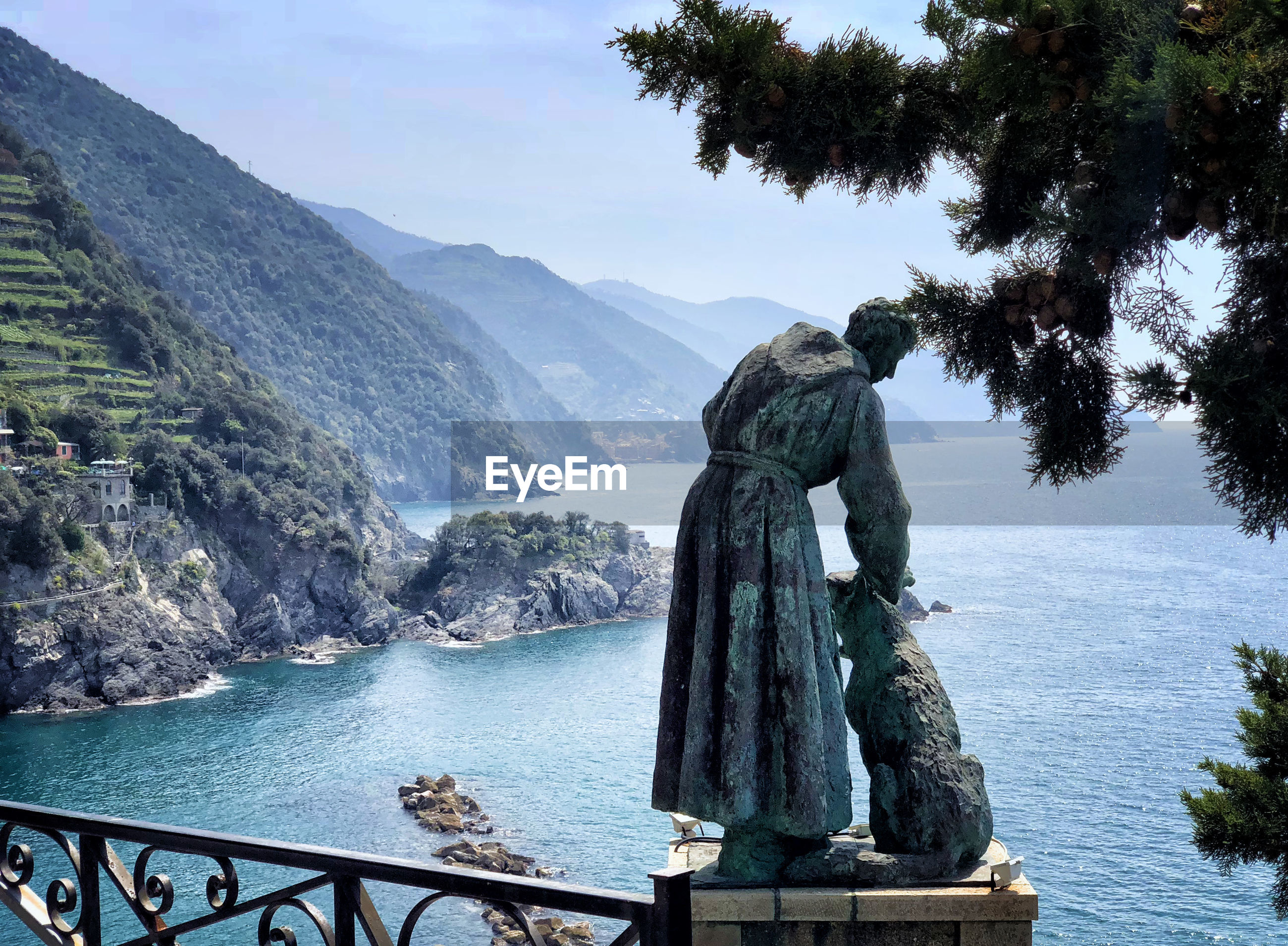 STATUE BY SEA AGAINST MOUNTAINS