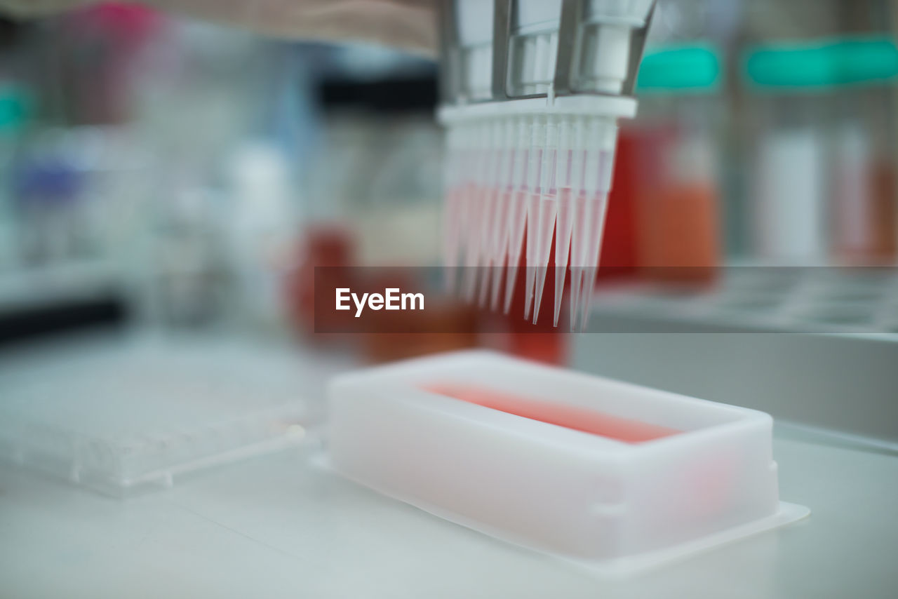 Pcr device pouring liquid in plastic container at laboratory
