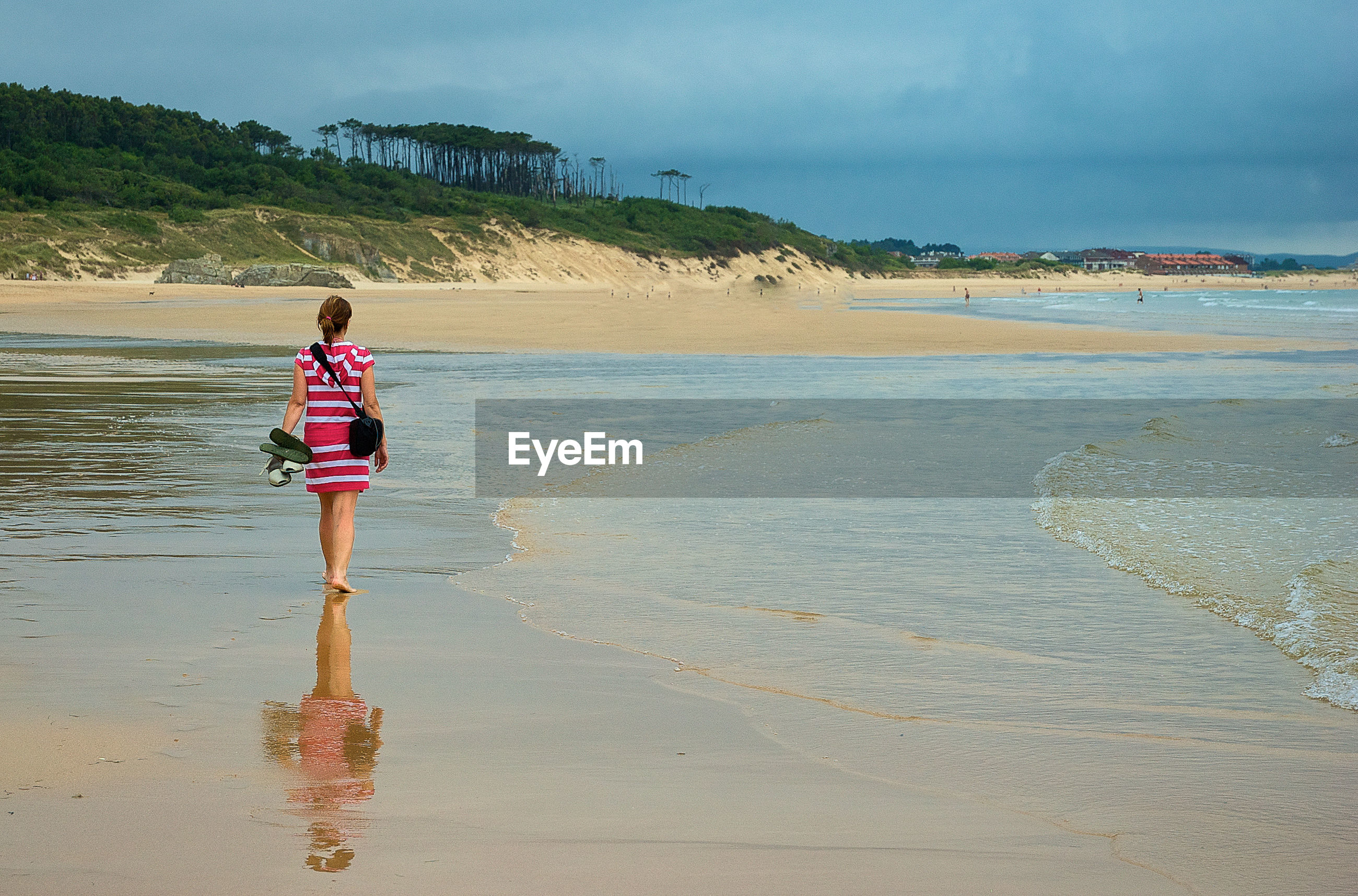 Rear view of woman walking on wet shore against cloudy sky