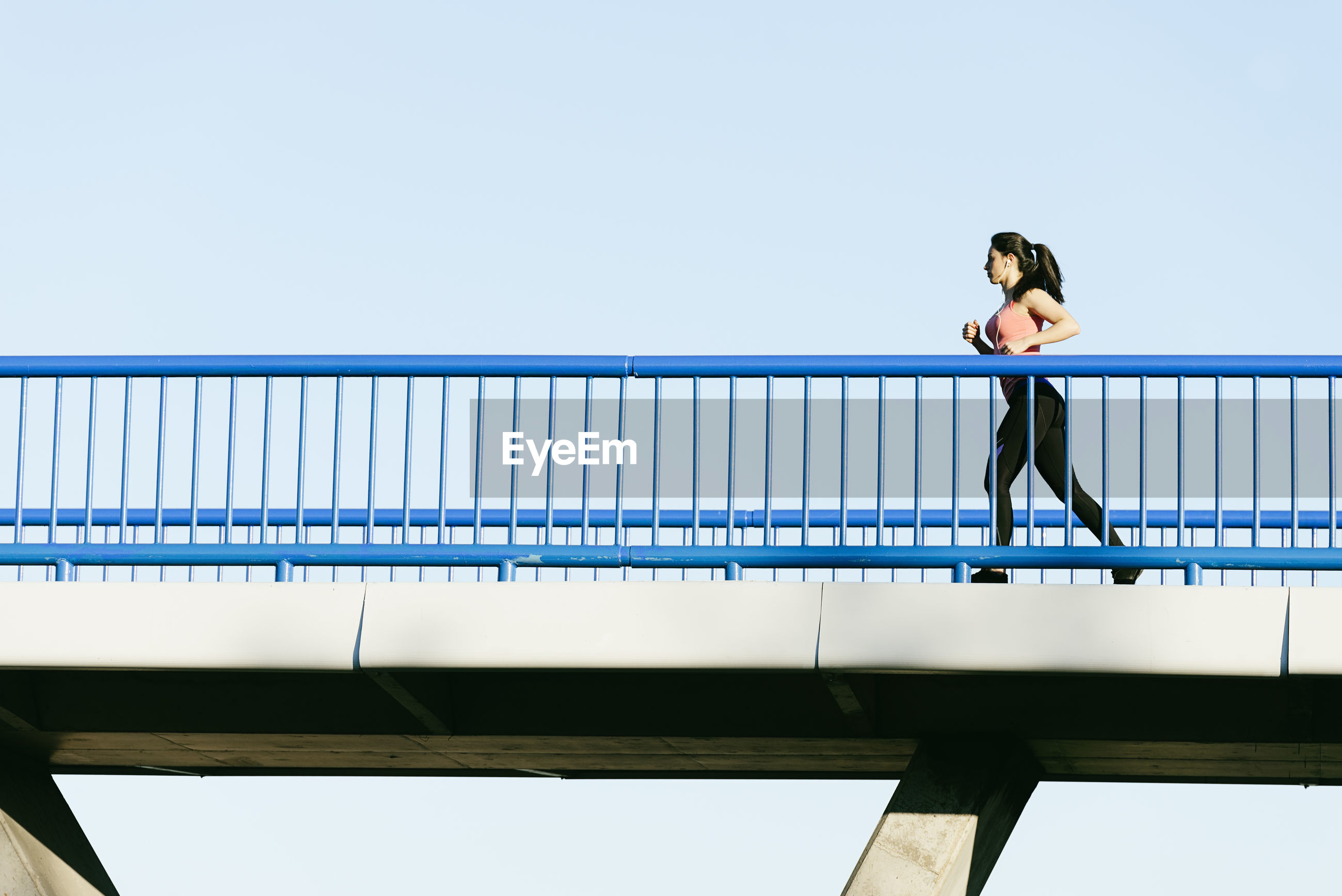 Low angle view of young woman running on footbridge against clear sky