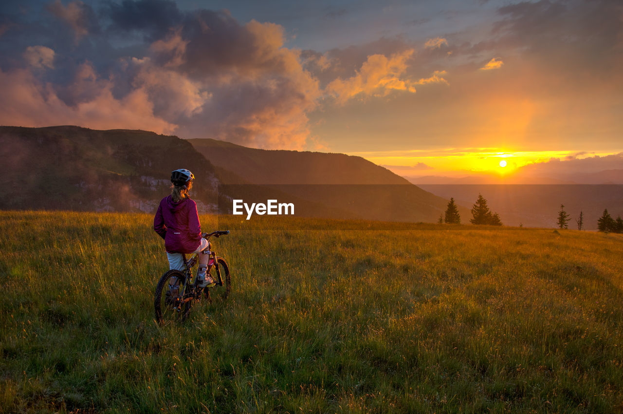 Woman With Bicycle On Field Against Sky During Sunset