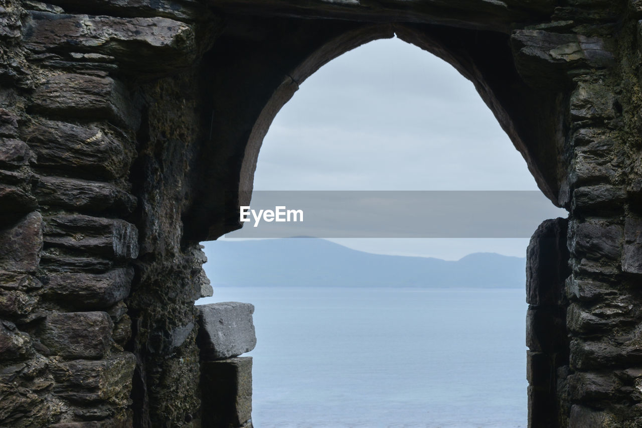 Sea seen through arch against sky