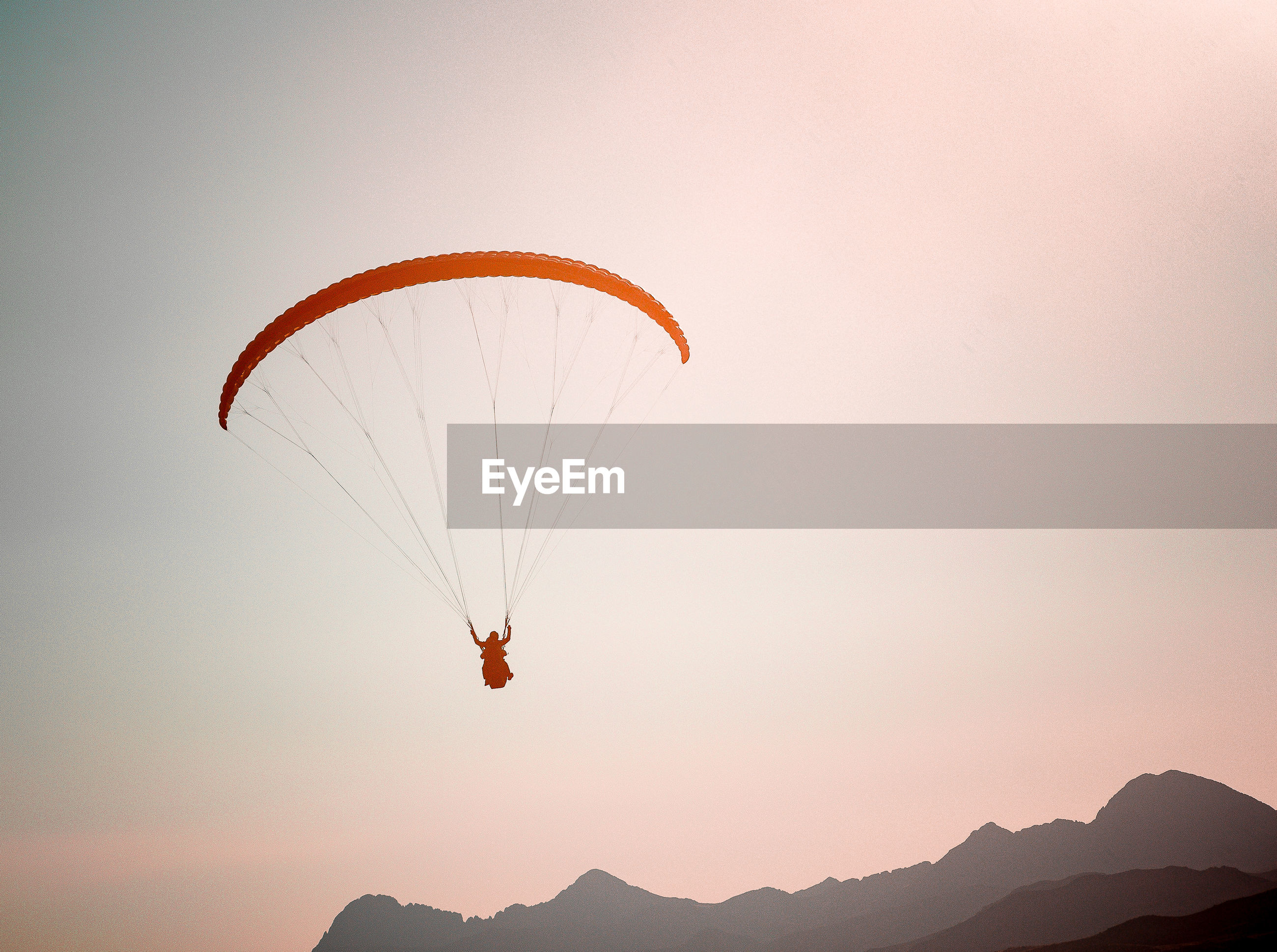 Low angle view of man paragliding against clear sky during sunset