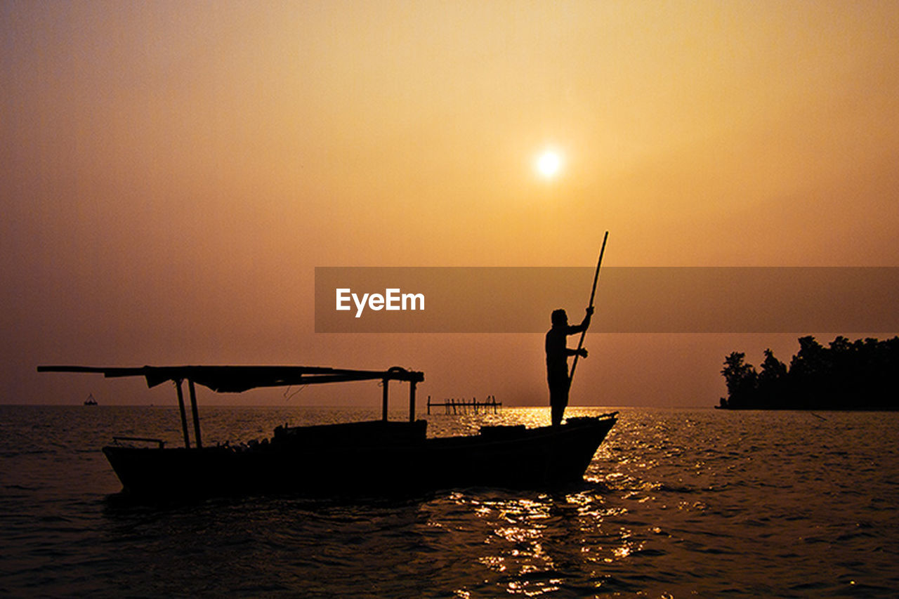 sunset, water, silhouette, nautical vessel, orange color, nature, real people, transportation, mode of transport, scenics, beauty in nature, sea, men, outdoors, waterfront, longtail boat, holding, sky, standing, lifestyles, fisherman, one person, day, people