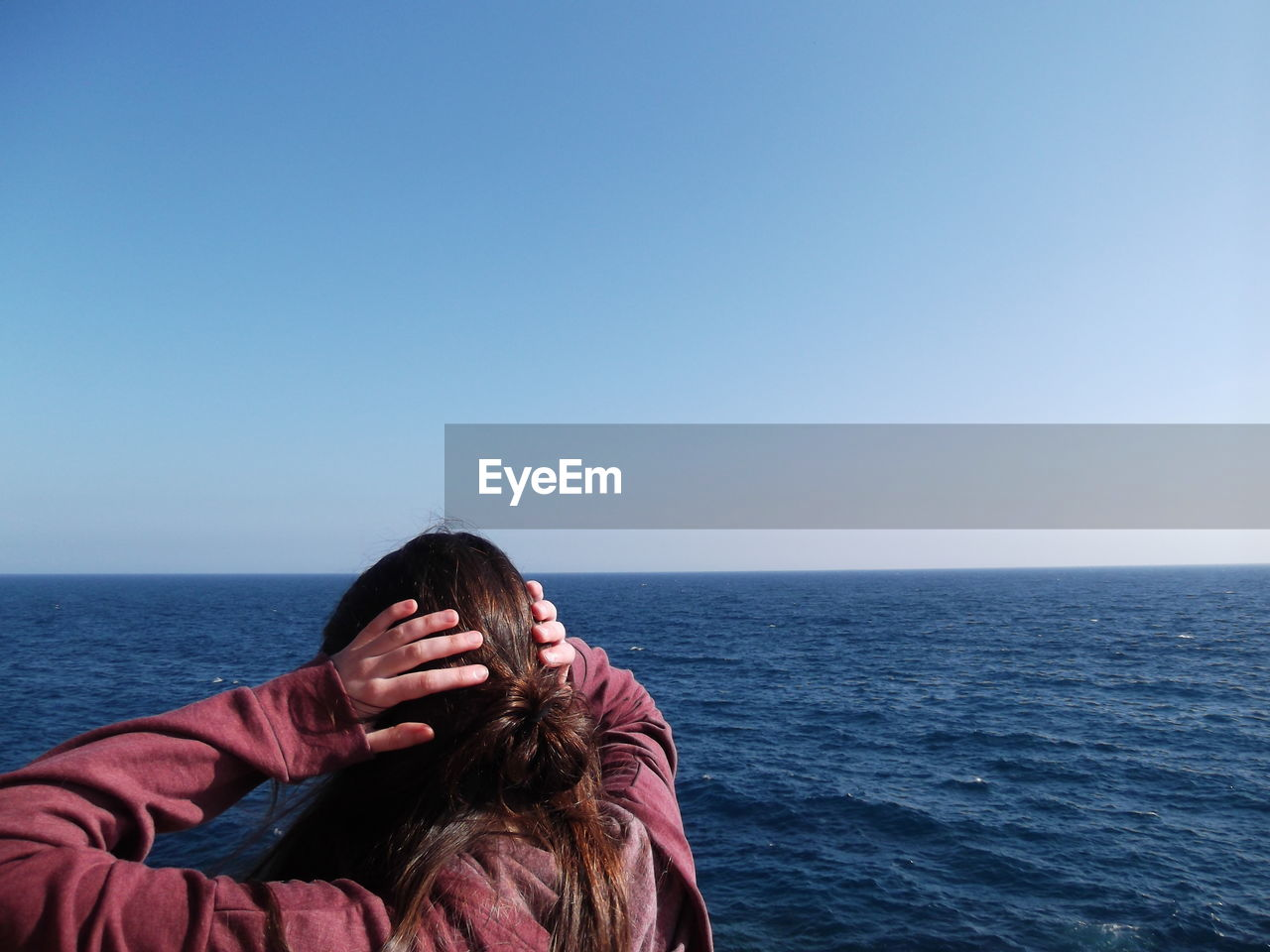 Rear View Of Woman By Sea Against Clear Sky