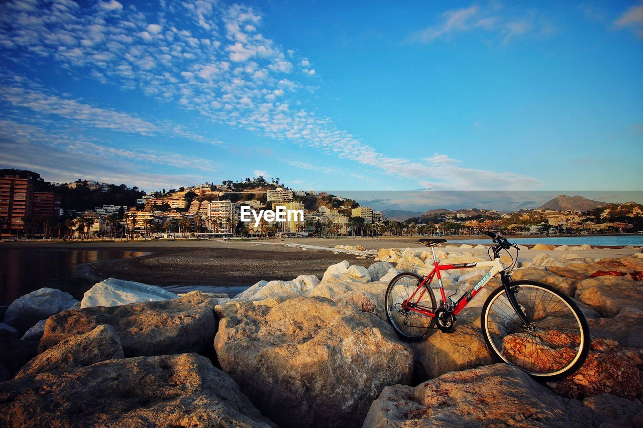 architecture, sky, building exterior, built structure, bicycle, outdoors, day, rock - object, transportation, mountain, no people, water, nature, retaining wall, city