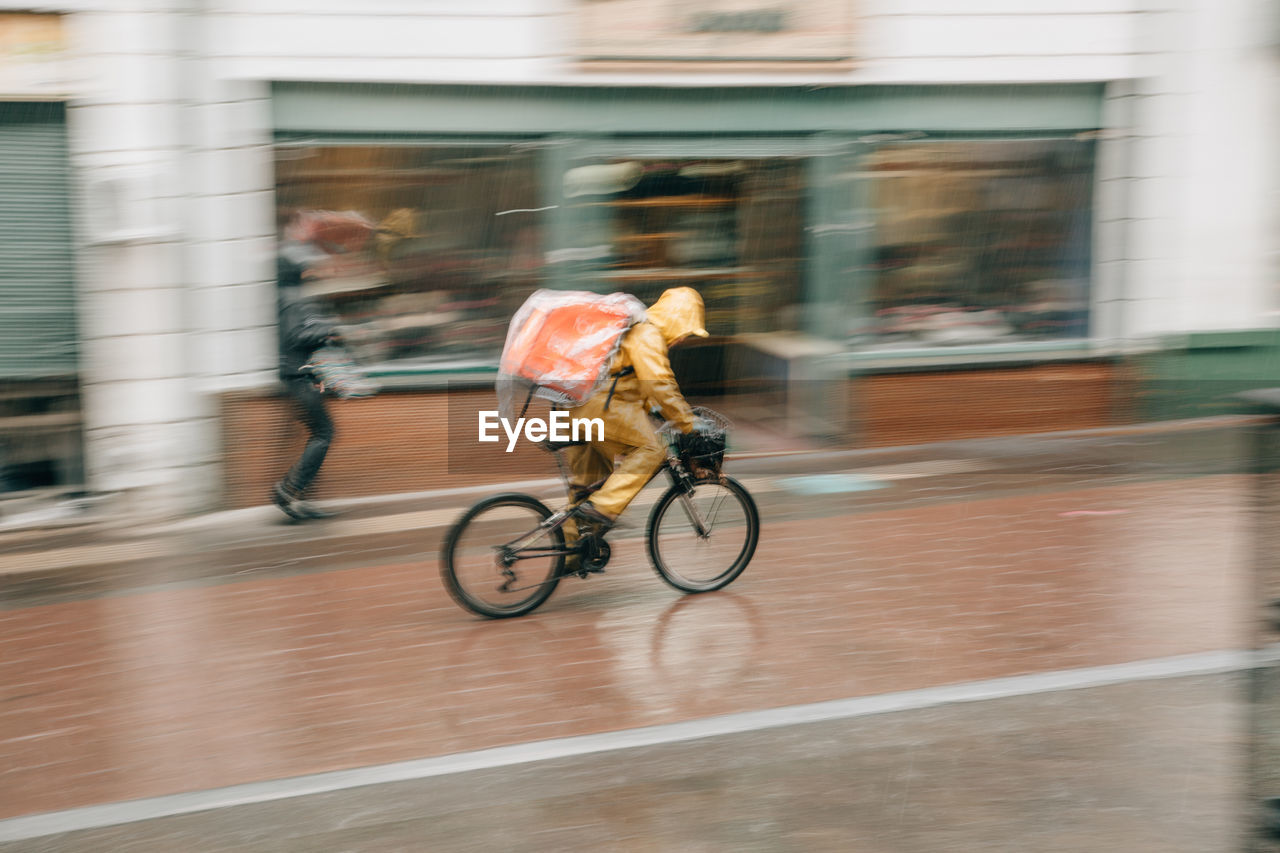 motion, blurred motion, transportation, bicycle, building exterior, built structure, city, architecture, sport, ride, real people, speed, activity, riding, lifestyles, day, mode of transportation, people, men, full length, outdoors