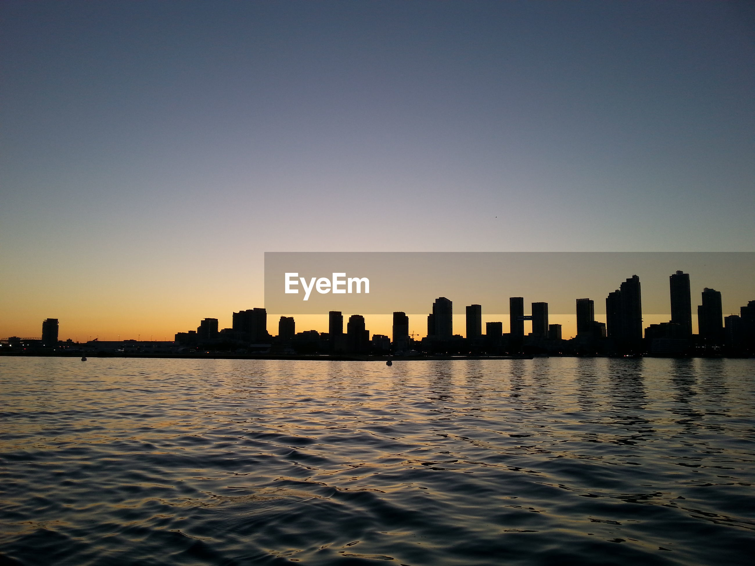 Scenic view of river against silhouette cityscape during sunset