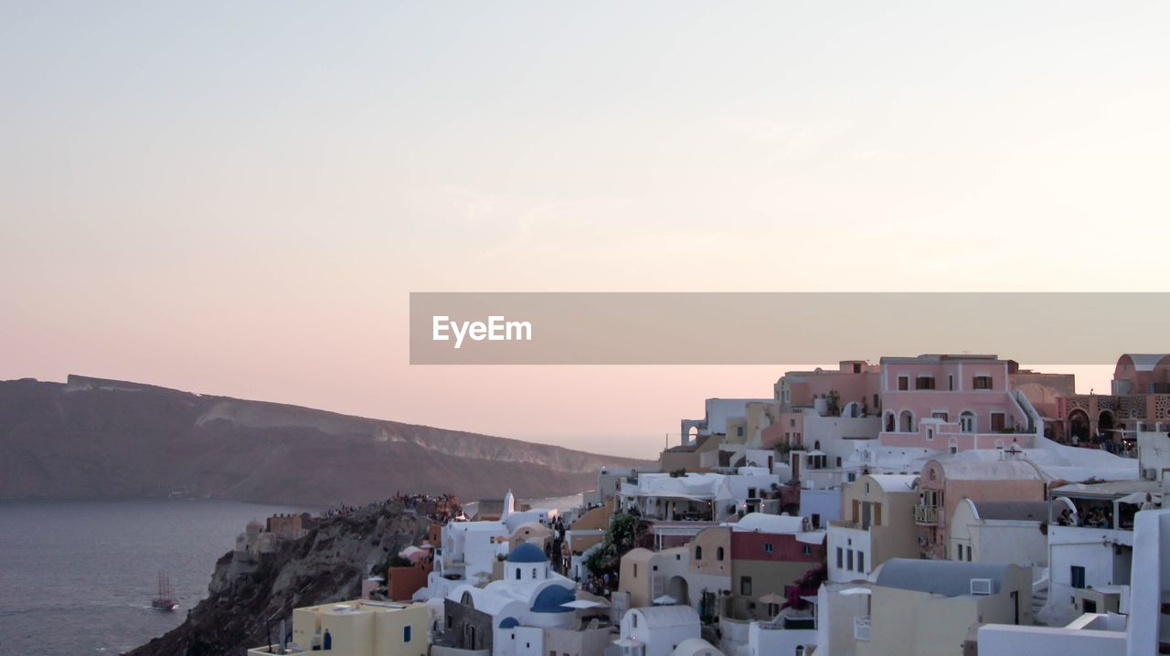 building exterior, architecture, built structure, sky, building, city, residential district, sunset, water, no people, nature, town, high angle view, mountain, sea, copy space, outdoors, cityscape, townscape
