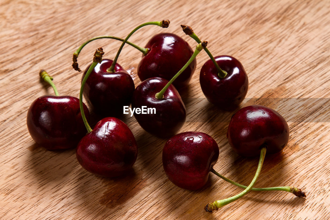 food, food and drink, healthy eating, fruit, wellbeing, freshness, red, still life, cherry, wood - material, indoors, close-up, table, no people, plant stem, group of objects, high angle view, focus on foreground, plant, ripe
