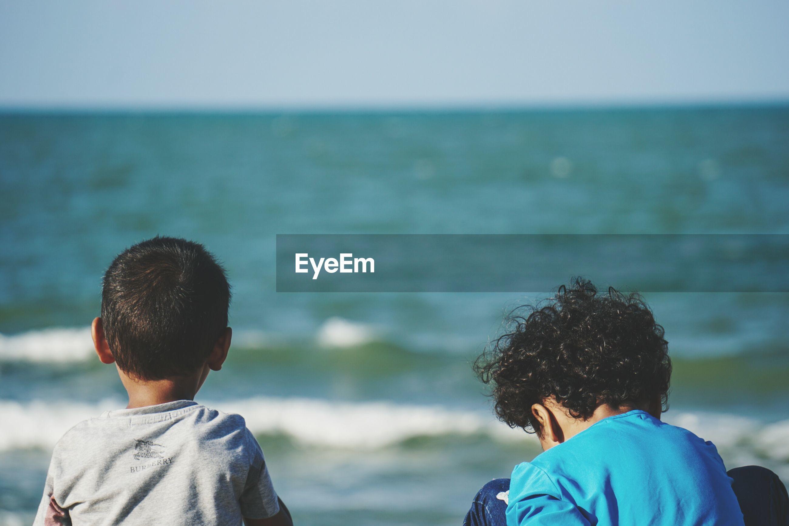 Rear view of siblings at beach