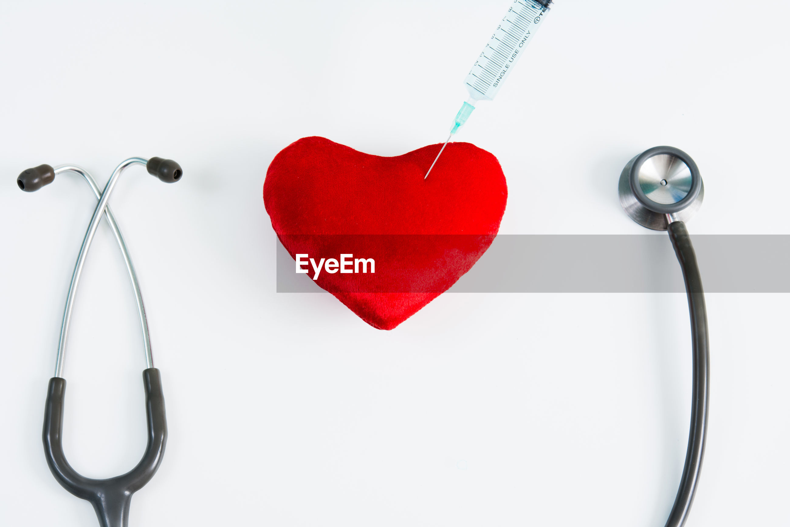 Close-up of heart shape and stethoscope against white background
