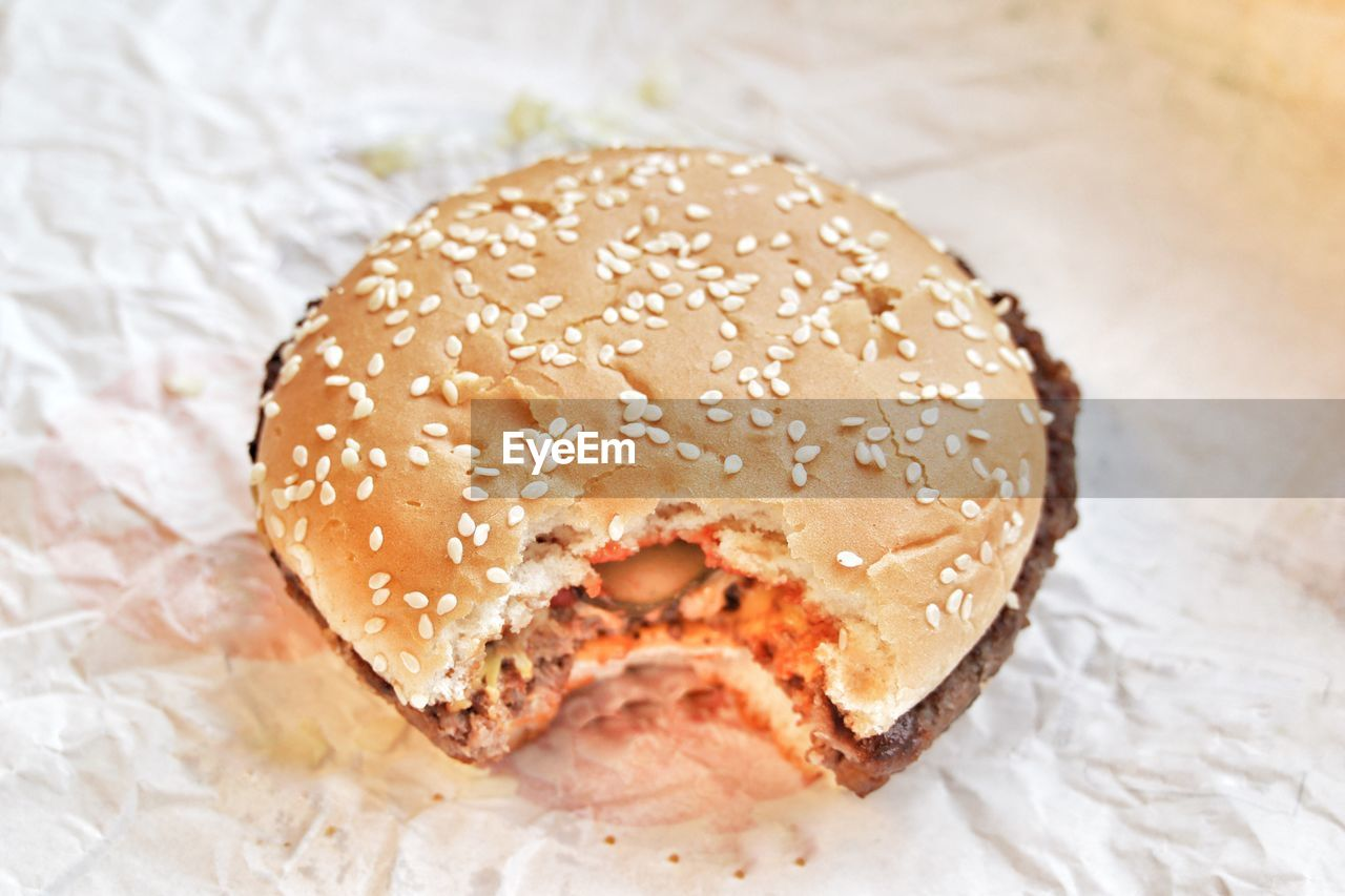 food and drink, unhealthy eating, food, bun, indoors, burger, still life, freshness, ready-to-eat, close-up, paper, indulgence, table, hamburger, fast food, focus on foreground, no people, take out food, temptation, sesame seed, sesame, wax paper, donut, sweet food, day