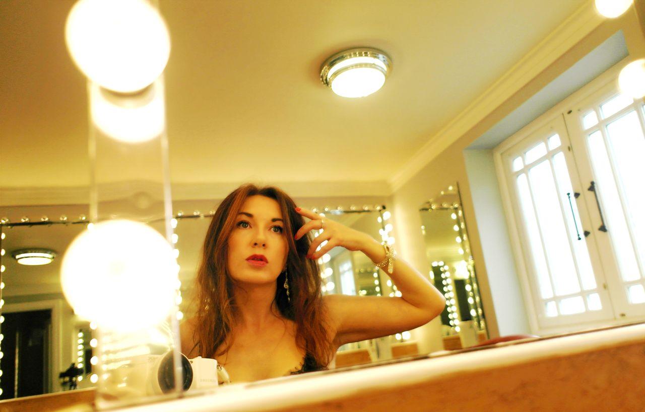 Reflection of woman applying make-up