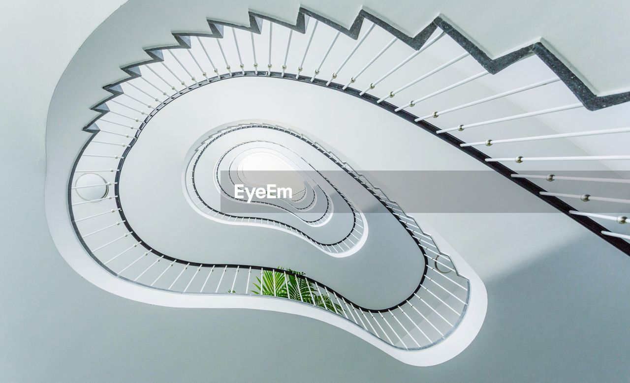 spiral, steps and staircases, staircase, spiral staircase, railing, architecture, built structure, pattern, low angle view, indoors, design, no people, directly below, building, white color, directly above, shape, day, swirl, electric lamp