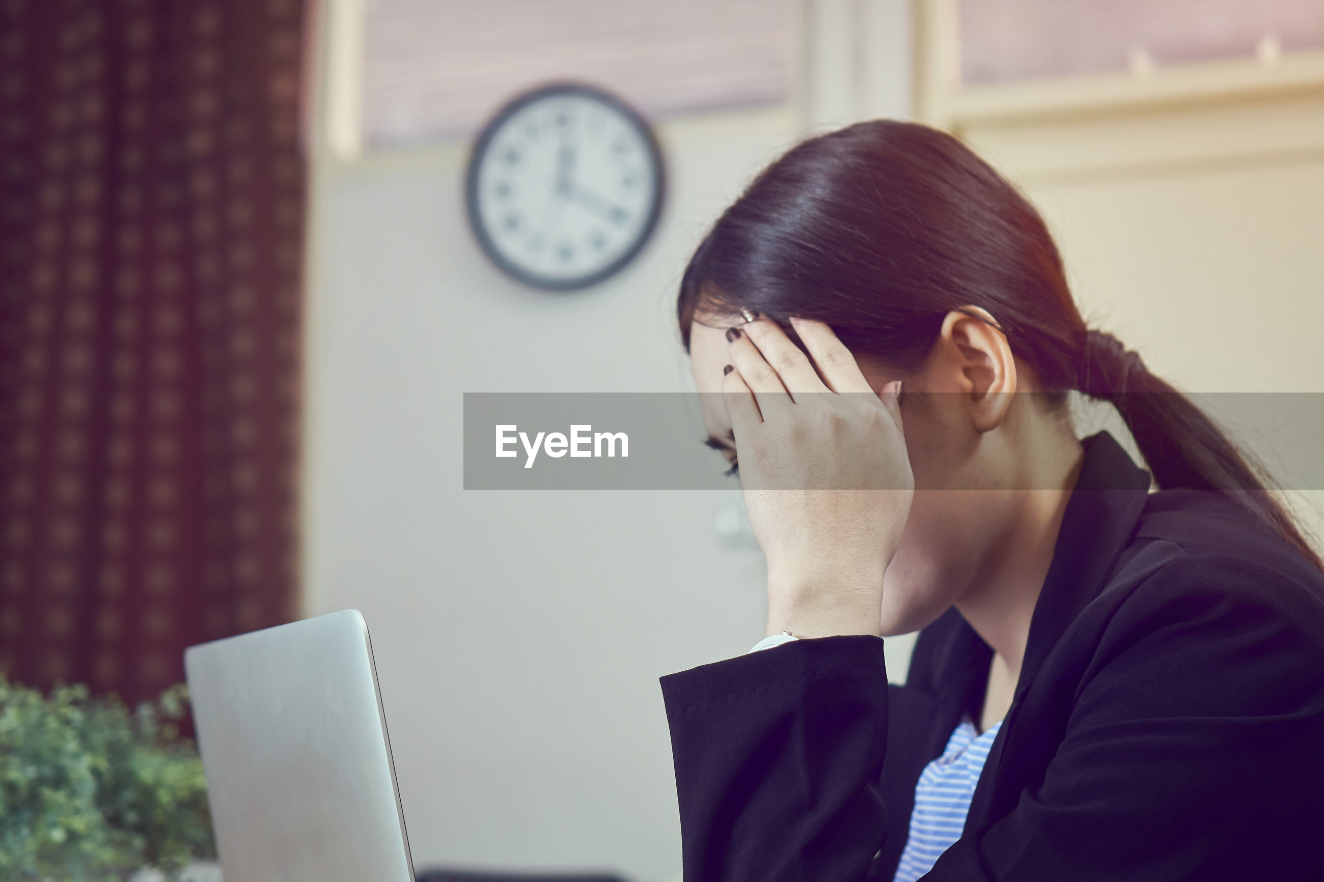 Businesswoman with headache using laptop in office