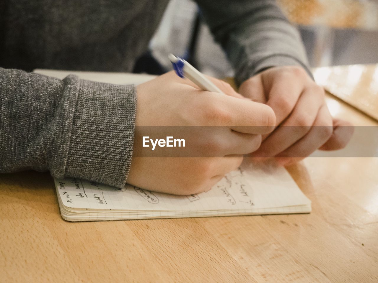 Cropped hand of person writing in book on table