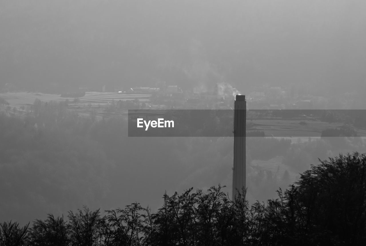 emitting, smoke - physical structure, outdoors, sky, industry, no people, smoke stack, factory, tree, day, low angle view, nature, architecture