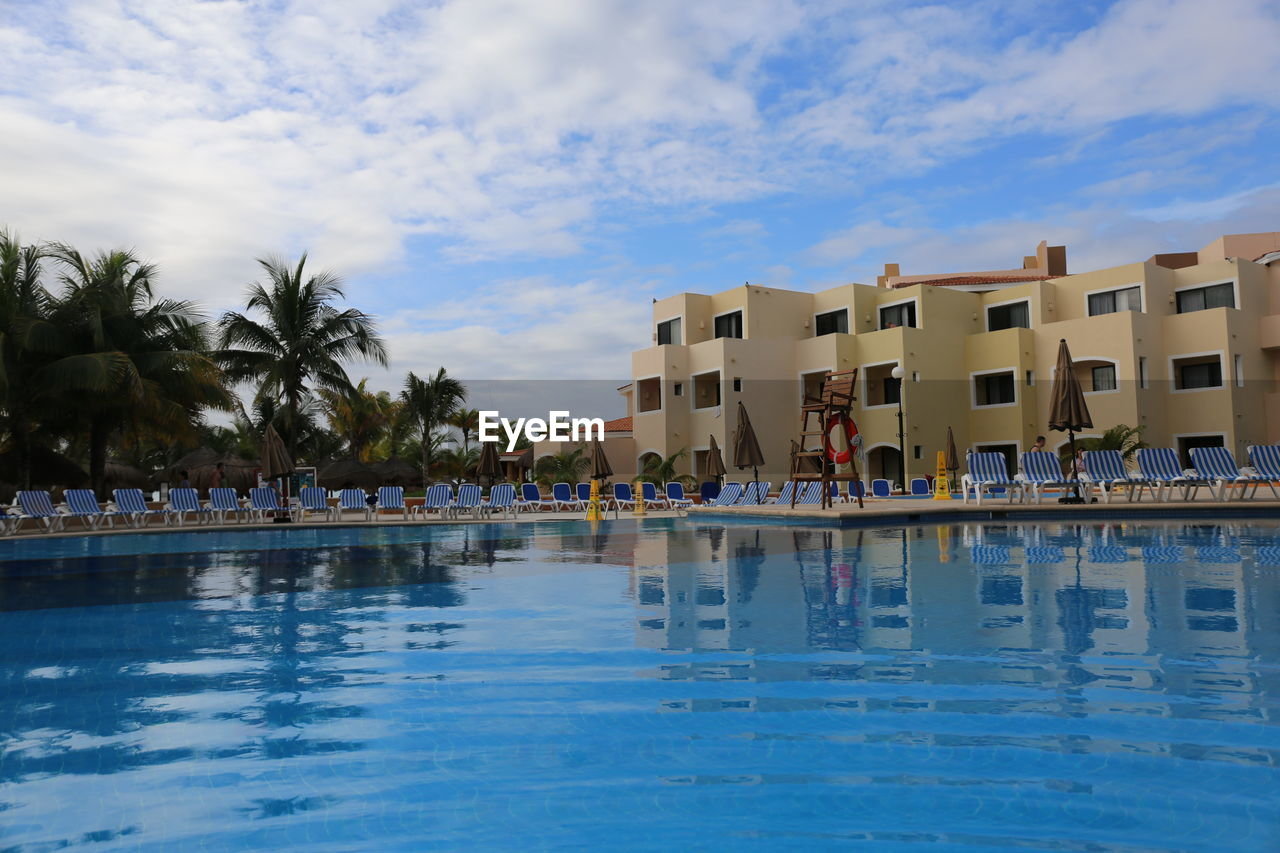swimming pool, water, real people, cloud - sky, sky, large group of people, vacations, palm tree, building exterior, built structure, architecture, outdoors, leisure activity, day, lifestyles, blue, men, travel destinations, nature, tree, people