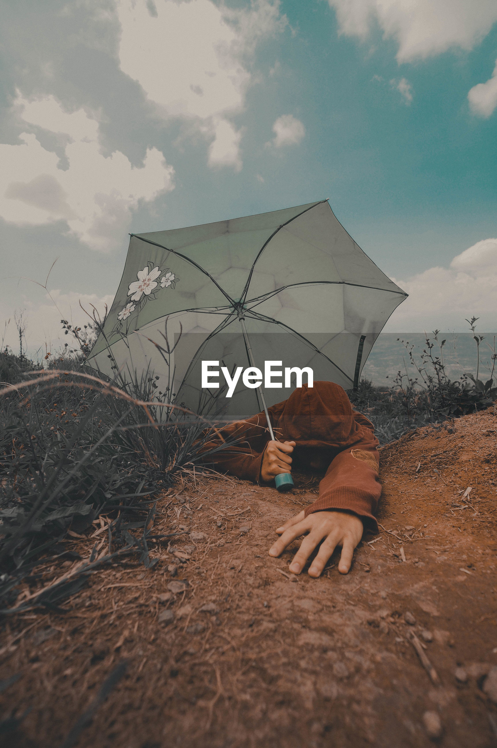 Tired man with umbrella on mountain against sky
